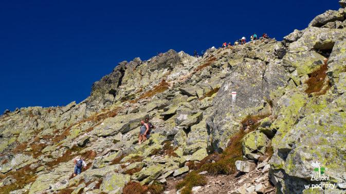 Szczyt już widoczny. Szlak poprowadzi nas wśród kamieni, a później po skałach